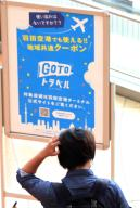 """October 1 2020, Tokyo, Japan - A tourist passes a notice board of governemnt\'s doestic travel campaign """"Go To Travel"""" at Tokyo\'s Haneda airport on Thursday, October 1, 2020 as Tokyo is included in the tourism promotion """"Go To Travel"""". (Photo by Yoshio Tsunoda\/AFLO"""