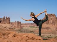 Young woman practices yoga at the La Sal Mountains Overlook in Arches National Park near Moab, Utah. In the background are the Courthouse Towers.