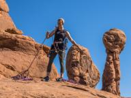 An attractive young woman prepares for a rock climb in the Garden of Eden in Arches National Park near Moab, Utah.