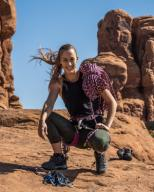 An attractive young woman poses with her rock-climbing gear in the Garden of Eden in Arches National Park near Moab, Utah.