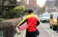 11 December 2019, Saxony-Anhalt, Halle: A DHL parcel deliverer takes two shipments to a house in the Paulus district. DHL expects a new record number of parcels for the days before Christmas. 11 million parcels are expected per day, the annual average is 5 million per day. In Halle, the Christmas season means 52,000 parcels, which are delivered to the front doors by 90 delivery staff every week. Photo: Jan Woitas/dpa-Zentralbild/
