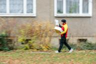 11 December 2019, Saxony-Anhalt, Halle: A DHL parcel delivery service delivers several shipments to a house in the Paulus district. DHL expects a new record number of parcels for the days before Christmas. 11 million parcels are expected per day, the annual average is 5 million per day. In Halle, the Christmas season means 52,000 parcels, which are delivered to the front doors by 90 delivery staff every week. Photo: Jan Woitas/dpa-Zentralbild/