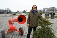 """26 January 2020, Hessen, Kassel: The Dutch artist Leon de Bruijne (r) stands with a Christmas tree in front of the Christmas tree canon (""""Kerstboomkanon""""). It can shoot fir trees up to 60 meters. The performance with the cannon is part of """"MODUS"""", the artist"""