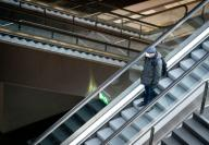 31 March 2020, Berlin: A man with a face mask is standing on an escalator in Berlin