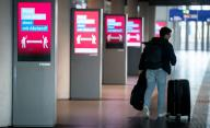 31 March 2020, Berlin: A man walks past illuminated signs at Berlin