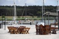 07 July 2020, Mecklenburg-Western Pomerania, Usedom: View over tables, chairs and benches to boats in the harbour of the town Usedom. The water hiking rest area with 70 places and a wide range of leisure activities was completed in 2019. The Usedomer-See-Zentrum is located on the eastern outskirts of the town on Usedom Lake, which can be reached from the Szczecin Lagoon via the access road between West and East Klüne. Photo: Stefan Sauer\/dpa-Zentralbild