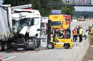 13 July 2020, Hessen, Butzbach: Firefighters have begun salvaging batteries after an accident on the A5 Kassel - Frankfurt near Butzbach. In the rear-end collision involving several trucks, batteries had been damaged and battery acid leaked. The A5 is closed for hours because of the clean-up work. Photo: Arne Dedert