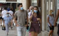 13 July 2020, Spain, Palma: A woman and a man with a mouth guard are walking in the centre of Palma. On Mallorca and the other Balearic Islands, an extensive compulsory wearing of masks will come into force on Monday due to the Corona pandemic. Photo: Clara Margais