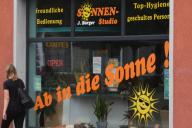 "16 July 2020, Mecklenburg-Western Pomerania, Torgelow: The lettering ""Ab in Sonne"" (Off to sun) is on the window of a tanning salon. The town is located on the lower Uecker in the area of the Ueckermünder Heide between the towns of Pasewalk and Ueckermünde. The small town, first mentioned in 1281, now has over 9,000 inhabitants and was once founded as a trading centre at the confluence of the Uecker and Randow rivers. Many apartments and shops in the old town are empty today. The traditional foundry, which is known above all for its components weighing several tons for large wind turbines and diesel engine construction, is threatened with insolvency. The foundry has about 320 employees and is considered one of the structure-determining companies for Western Pomerania. Photo: Stefan Sauer\/dpa-Zentralbild"