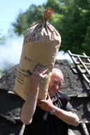 21 May 2020, Saxony-Anhalt, Hasselfelde: Ulrich Engel fills charcoal into sacks. In the Harz charcoal plant, visitors are shown the old craft in a vivid way. The Harz charcoal plant produces over 50 tons of charcoal annually. It is one of the last charcoal-fired companies still operating the old craft in Germany. Photo: Matthias Bein\/dpa-Zentralbild