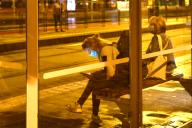 A young woman sits with a face mask, mask at a bus stop, tram stop, bus stop and looks at her smartphone, which illuminates her face, aftertake, on 09\/23\/2020. | usage worldwide