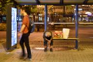 A homeless man sits bent forward at a bus stop - next to him are two plastic bags - a passerby, young man walks past. aftertake, on 09\/23\/2020. | usage worldwide