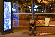 A homeless man sits bent forward at a bus stop, next to him are two plastic bags. aftertake, on 09\/23\/2020. | usage worldwide