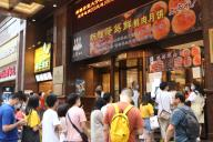 A group of customers queue in the line, waiting to buy mooncake from a local famous store, which sells not only traditional Shanghai mooncake with meat inside, but also innovated mooncake with goose liver inside, Shanghai, China, 11 July 2020. Local Caption