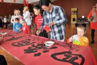 (200126) -- HOUSTON, Jan. 26, 2020 (Xinhua) -- People try Chinese calligraphy during Chinese Lunar New Year celebrations in Houston, the United States, on Jan. 25, 2020. The Asia Society Texas Center in Houston held Chinese Lunar New Year celebrations Saturday. Local Americans and Chinese participated in the event. (Xinhua/Liu Liwei)