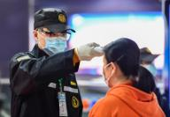 (200126) -- GUANGZHOU, Jan. 26, 2020 (Xinhua) -- A security personnel checks a passenger