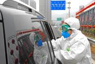 (200126) -- LIANYUNGANG, Jan. 26, 2020 (Xinhua) -- A staff checks a passenger