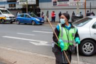 (200331) -- JOHANNESBURG, March 31, 2020 (Xinhua) -- A cleaner wearing a mask works on the street in Johannesburg, South Africa, March 30, 2020. (Photo by Yeshiel Panchia/Xinhua)