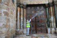 (200331) -- JERUSALEM, March 31, 2020 (Xinhua) -- A worker cleans the locked door of the Church of the Holy Sepulchre in Jerusalem