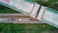 (200924) -- XIAMEN, Sept. 24, 2020 (Xinhua) -- Aerial photo shows a high-speed train running under a swivel bridge of the Fuzhou-Xiamen railway in Quanzhou, southeast China\'s Fujian Province, Sept. 24, 2020. The two 168-meter-long and 19,000-tonne girders of a grand bridge of the Fuzhou-Xiamen railway were successfully rotated to their targeted positions on Thursday. The railway, linking Fujian\'s capital of Fuzhou and city of Xiamen, has a designed speed of 350 km\/h and is expected to be put into operation in 2022. (Xinhua\/Song Weiwei