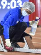 (200926) -- DOHA, Sept. 26, 2020 (Xinhua) -- A staff member wearing a protective face mask disinfects the starting blocks during the 2020 Diamond League Athletics Meeting in Doha, Qatar, Sept. 25, 2020. (Photo by Nikku\/Xinhua