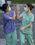 New coronavirus Medical workers in protective gear high-five each other after completing a shift for the service of people infected with the new coronavirus at a hospital in the southeastern city of Daegu, the epicenter of South Korea